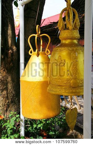 Two golden bells in temple, different styles, bigger one in sunlight.