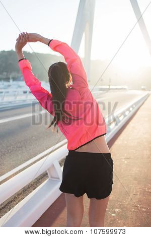 Athletic woman with perfect slim body working out while standing on running road