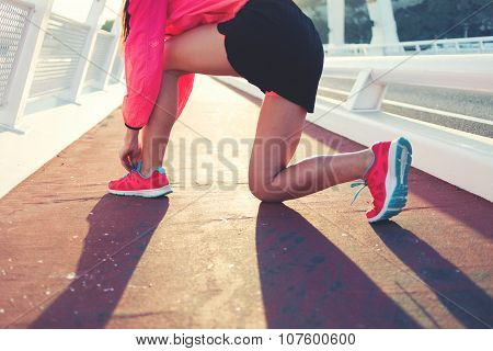 Cropped shot view of young sporty girl tie shoelaces while standing on a road in summer evening