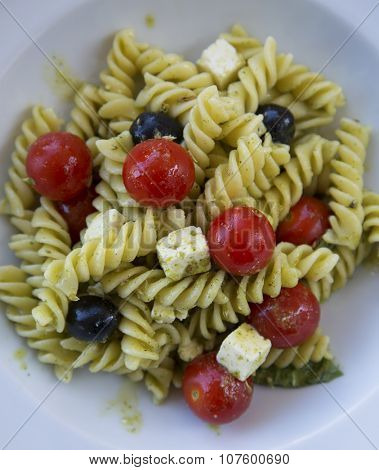 Fresh fusilli pasta with cherry tomato, black olives and feta cheese