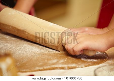 Working on unfinished dough with a rolling pin