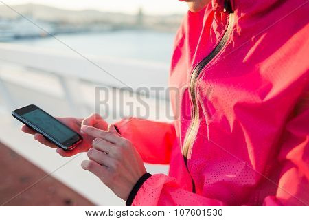 Fit woman using cell telephone while resting after evening jog outdoors