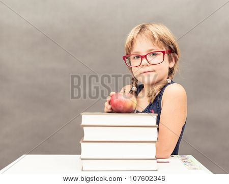 Schoolgirl Wearing Glasses Sitting At A Table With A Stack Of Thick Books And An Apple On Top