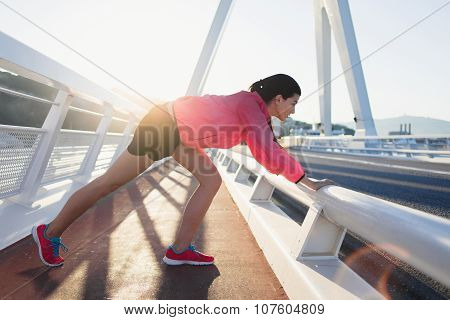 athletic female doing warm up exercises in the fresh air in summer evening