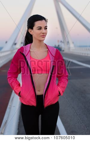 Young charming dreamy fit woman relaxing after her workout