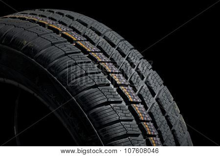 Winter tyre closeup, dark backgroud