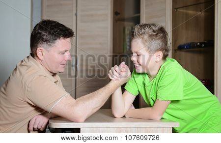 Photo of boy and his dad competing in physical strength. Father arm wrestling with his son - happy f