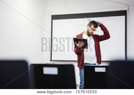 Young teacher with beard in brown hoodie thinking in empty classroom near the whiteboard