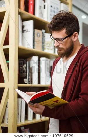 Handsome young student in glasses and brown hoodie reading book in library