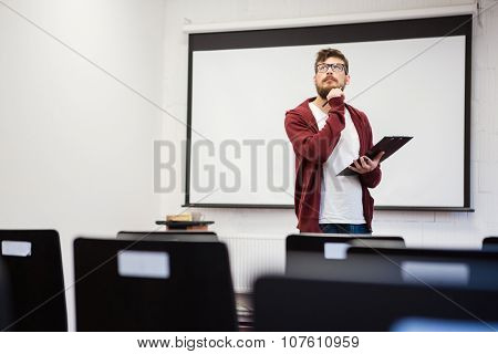 Young modern teacher with beard preparing for the lecture in classroom