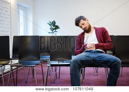 Young man with beard in brown hoodie and blue jeans falling asleep at conference room