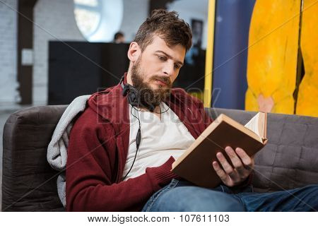 Serious handsome clever guy sitting on gray sofa and reading a book