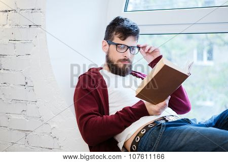 Young handsome man in glasses and brown hoodie reading on the window sill