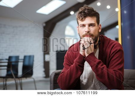 Handsome serious young man in brown sweetshirt is sitting ang holding glasses