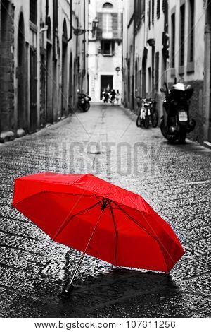 Red umbrella on cobblestone street in the old town. Wind, rain, stormy weather. Color in black and white conceptual, idea. Vintage, retro style.