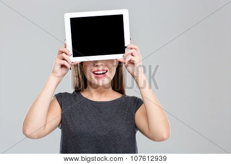Portrait of a happy woman covering her eyes with blank tablet computer screen isolated on a white background