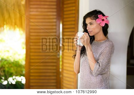 portrait of a young woman looking away and  enjoying in hot cup of coffee or tea