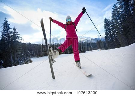 carefree young woman in ski suit jumping