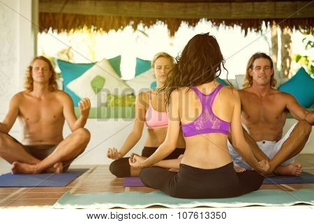 People sitting in lotus position and practicing yoga