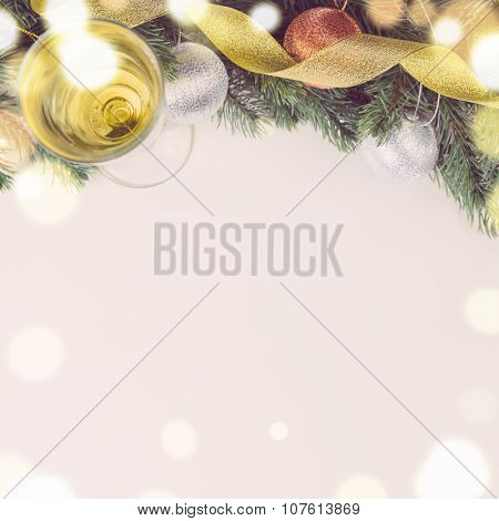 glass of sparkling wine and decorative christmas balls with fir tree on white surface, view from above