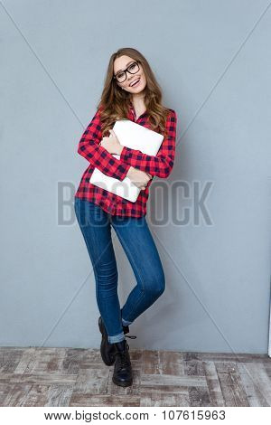 Cheerful beautiful amusing girl in glasses, jeans and plaid shirt posing and smiling hugging laptop