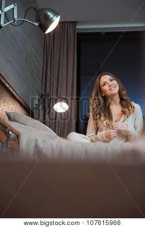 Cute curly happy cheerful girl smiling sitting on big beige bed