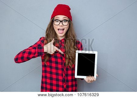 Portrait of a cheerful hipster woman pointing finger on tablet computer screen over gray background
