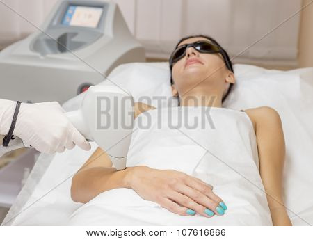 Laser hair removal on ladies hand in beauty salon