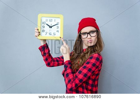 Portrait of a cute hipster woman pointing finger on wall clock over gray background