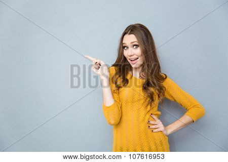 Portrait of a smiling casual woman pointing finger away over gray backgorund