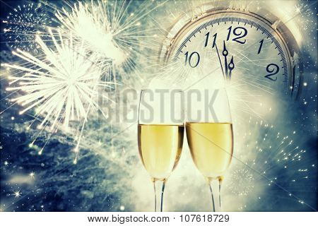 Glasses with champagne against holiday lights and clock close to midnight