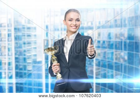 Portrait of businesswoman keeping golden cup and thumbing up, blue background. Concept of victory and success