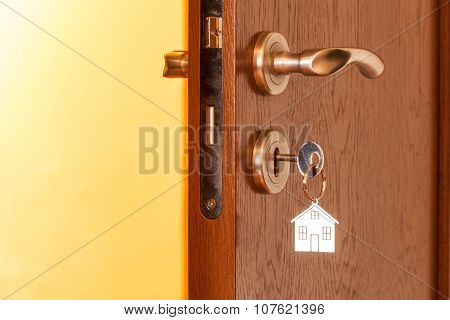 Door Handle With Inserted Key In The Keyhole And House Icon On It