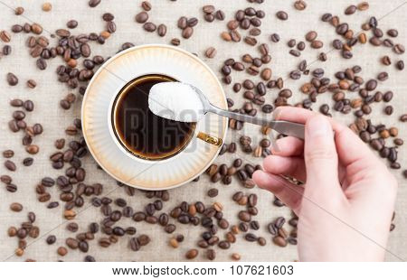Young Man Adds Sugar In Coffee. Top View.