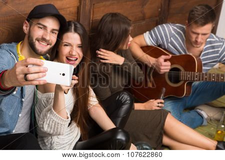 Happy friends making selfies and playing the guitar