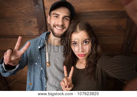 Happy friends making selfies isolated on wooden background