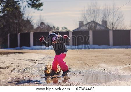child girl in waterproof pants playing and jumping in puddle on the walk