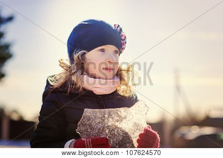 child girl playing with block of ice in early spring