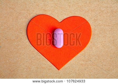 Red paper heart shape over craft paper with one small pink pill on.