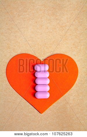Red paper heart shape over craft paper with row of small pink pill on. Heart health.