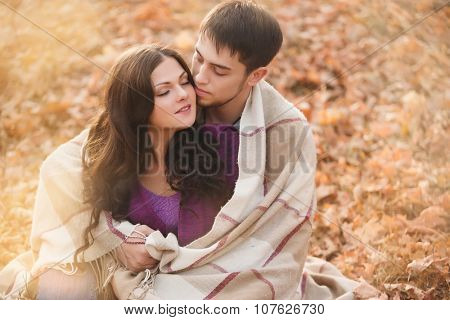 couple in love wrapped in a blanket in the autumn forest