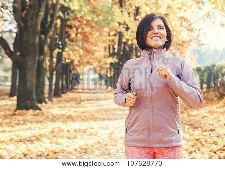 Running woman in the autumnal park