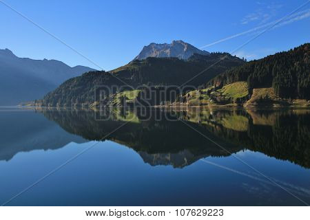 Mountains And Forest Reflecting In Lake Wagital