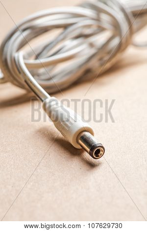 Laptop AC adapter plug on brown craft paper