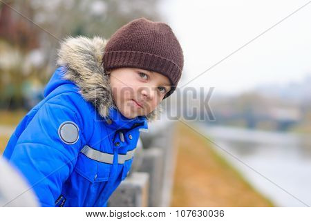 Boy In Blue Jacket Leans On The Railing Of The Fence
