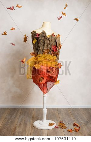 Mannequin dressed with tree bark and autumn leaves - leaves falling in background