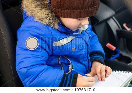 Boy Writes In Notebook Sitting Inside The Car
