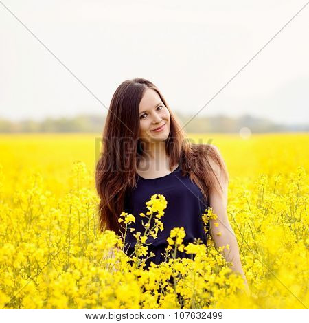 Portrait of young beautiful long hair brunette wearing sleeveless dress and smiling over yellow blooming rapeseed meadow