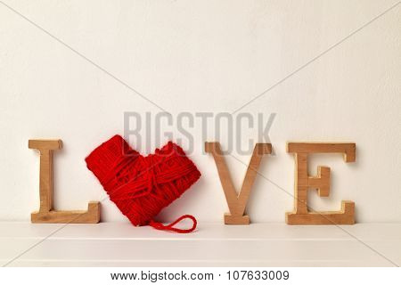 some wooden letters and a heart-shaped coil of red yarn forming the word love