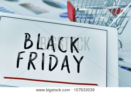 the text black friday written in the screen of a tablet computer and a shopping cart in the background